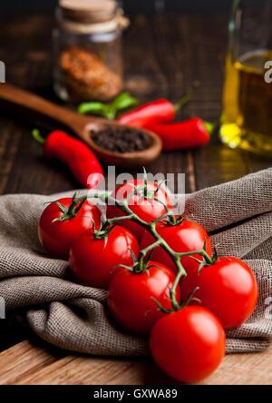 Frische Tomaten mit roten und schwarzen Pfeffer auf Küchentuch und Küche-Board. Glas mit Olivenöl und Gewürzen auf - Stockfoto
