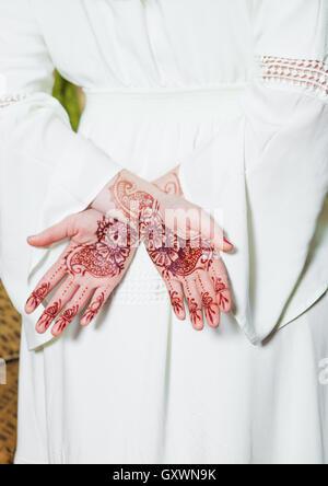 Mädchen hält Hände mit Henna-Tattoos auf weißen Kleid - Stockfoto