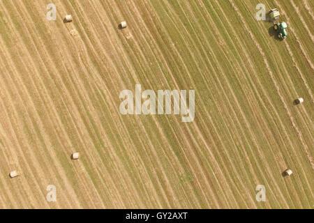 Luftaufnahme des Traktors mit Rundballenpresse Strohballen auf abgeernteten Feld Rollen - Stockfoto