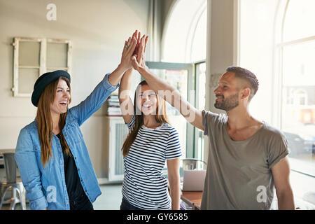Glücklich begeisterte Geschäftspartner dabei eine hohe Fives Geste, wie sie einen Erfolg im Büro, trendige junge - Stockfoto