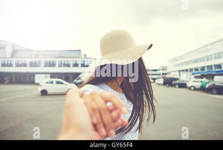 Frau mit ausgestreckten Hand wendet sich von der Kamera beim Tragen der Strohhut und stehen auf dem Parkplatz - Stockfoto