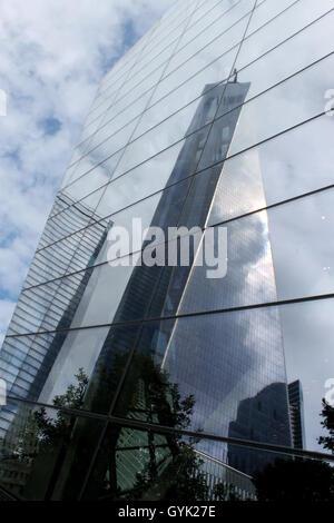 Das neue One World Trade Center reflektiert von den Fenstern des 9/11-Museums in Lower Manhattan, New York City - Stockfoto