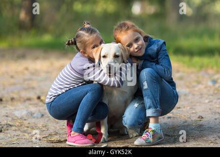 Zwei kleine Mädchen mit dem Hund im Freien. - Stockfoto