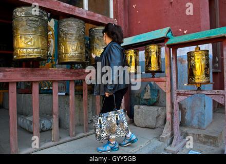 Mongolische Frau drehen buddhistischen Gebet Mühlen im Gandantegchinlen Kloster, Ulaanbaatar, Mongolei - Stockfoto