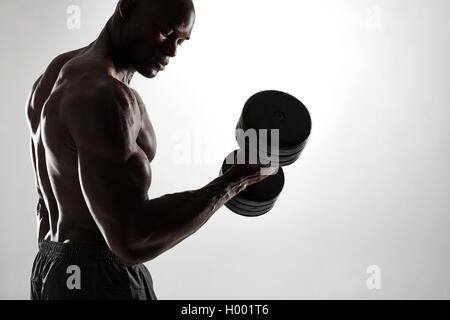 Silhouette von gesunden muskulösen jungen Mann Workout mit Kurzhanteln vor grauem Hintergrund. Bodybuilder Training - Stockfoto