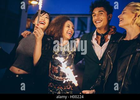 Aufnahme des jungen Menschen und Frauen in der Stadt bei Nacht mit Feuerwerk. Gruppe von Freunden mit Wunderkerzen - Stockfoto