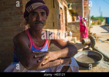 GODWAR REGION, Indien - 14. Februar 2015: Mechaniker mit Schnurrbart tragen Kopftuch und große goldene Ohrringe - Stockfoto