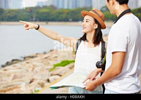 junge asiatische paar Touristen versuchen, eine Landschaft vor Ort mit Hilfe einer Karte lokalisieren - Stockfoto