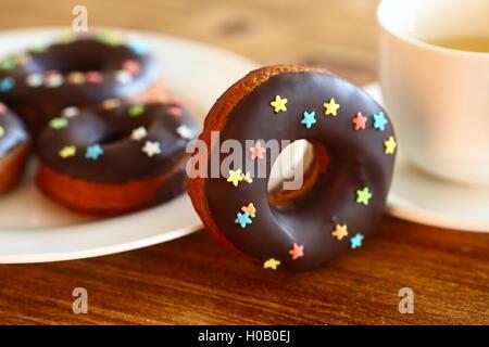 Schokolade Donut mit Wachspapier und Getränk auf Holztisch