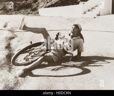 Frau, die ihr Fahrrad am Straßenrand herunterfallen - Stockfoto