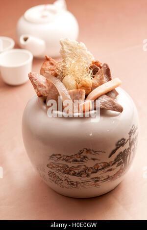 Chinesische Kräuter-Tee mit getrockneten Pilzen und Drogen im weißen Topf - Stockfoto
