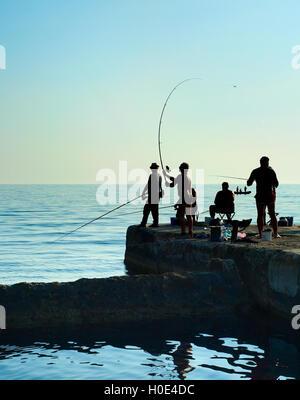 Gruppe von Fischern auf einem Pier bei Sonnenuntergang. Halbinsel Krim - Stockfoto