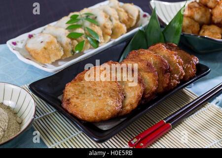 Gebratener Fischkuchen auf schwarzen Druckplatte auf Bambus-Tablett in restaurant - Stockfoto