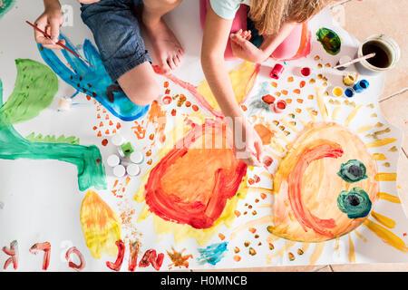 Kinder malen zusammen auf einem großen Blatt Papier - Stockfoto