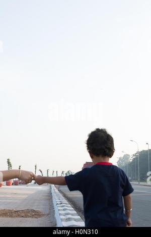 kleiner Junge hält seine Mutter Hand zur Unterstützung beim gehen auf dem Weg am Tank Bund Road in Hyderabad, Indien - Stockfoto