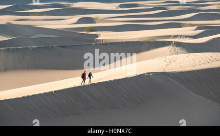 Zwei Menschen zu Fuß auf Sanddünen, Mesquite flachen Sand Dünen, Death Valley, Death Valley National Park, Kalifornien, - Stockfoto