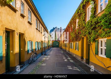 Mit Blick auf Wände in gelber Farbe und grünen Fensterläden an der Fuggerei Häuser in Deutschland - Stockfoto
