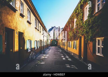 Fahrrad in der Fuggerei tief gelbe Wand gelehnt Häuser mit Tor am Ende in Deutschland - Stockfoto