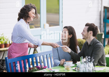 paar zahlenden Kellnerin Café im freien - Stockfoto