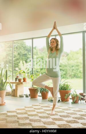 Schwangerschaft Frau praktizieren Yoga Baum darstellen - Stockfoto