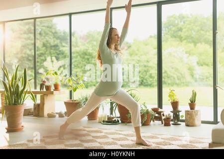 Schwangere Frau praktizieren Yoga Krieger 1 stellen - Stockfoto