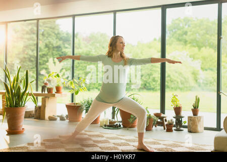 Schwangere Frau praktizieren Yoga Krieger 2 stellen - Stockfoto