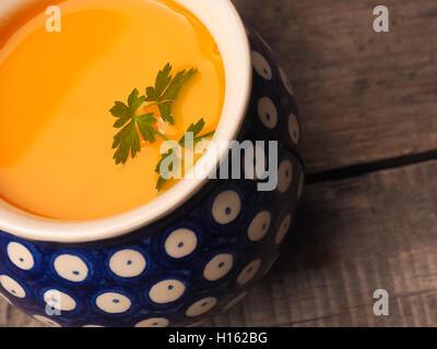 Schuss von Hokkaido Creme Suppe auf einem Holztisch hautnah - Stockfoto