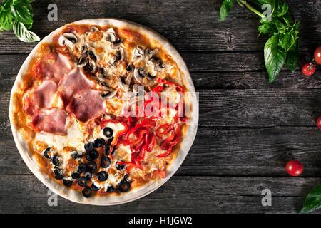 4 Teile köstliche frische Pizza mit Speck, Champignons, Paprika und Oliven auf dem hölzernen Hintergrund sortiert. - Stockfoto