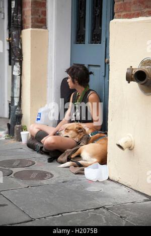 Eine Frau sitzt auf der Straße vor einem Eingang in das French Quarter von New Orleans, begleitet von ihrem Hund. - Stockfoto