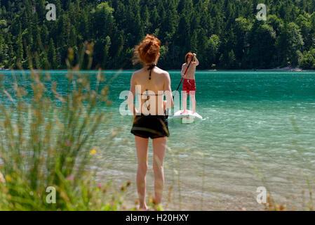 Österreich, Tirol, Ammergauer Alpen, Plansee, Teenage Boy auf Paddleboard, Schwester warten am Ufer stehen - Stockfoto
