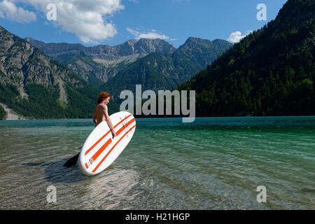 Österreich, Tirol Ammergauer Alpen, Plansee, Teenager mit paddleboard - Stockfoto