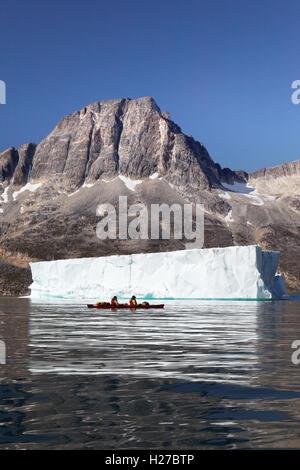 Meer-Kanuten Paddeln auf Ikaasatsivaq Fjord unter Berg- und tabellarische Eisberg, Insel Ammassalik, Ostgrönland - Stockfoto