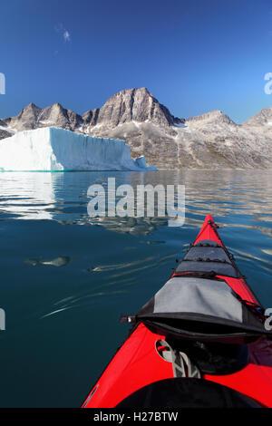 Kajakfahrer Meer paddeln auf Ikaasatsivaq Fjord unter Berg- und tabellarische Eisberg, Insel Ammassalik, Ostgrönland - Stockfoto
