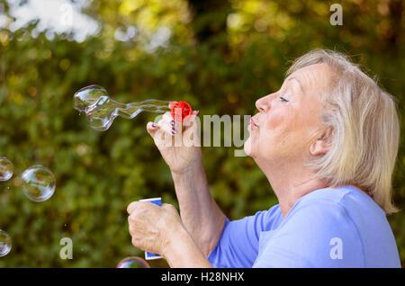 Höhenplan der attraktive ältere Frau irisierenden Glanz Seifenblasen durch einen roten Kunststoff Ring im Freien - Stockfoto