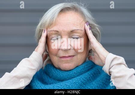 Senior Frau hält ihre Hände, ihre Tempel mit ihren Augen geschlossen, da sie einen ruhigen Moment, de-Stress von - Stockfoto