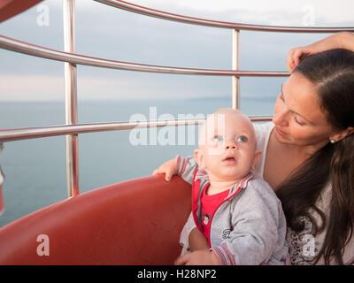 Junge Mutter mit ihrem kleinen Sohn spielen im Freien auf Riesenrad - Stockfoto