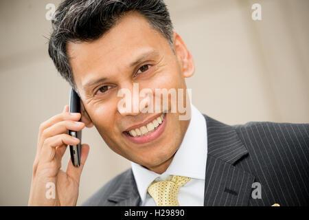 Lächelnde asiatische Geschäftsmann auf seinem Handy zu sprechen. - Stockfoto