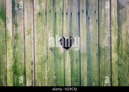 Herzform Ausschneiden auf Holzwand - Stockfoto