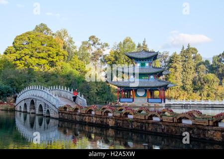 Orientalische Frau Tourist auf Bogenbrücke im Black Dragon Pool in Lijiang, China - Stockfoto