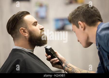 Profilbildnis Ansicht hübscher junger bärtige kaukasischen Mann immer Bart Pflege in modernen Friseursalon. Friseur - Stockfoto