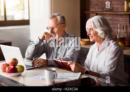 Gerne älteres Paar mit Laptop in der Küche - Stockfoto
