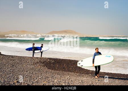 Junge Surfer mit Surfbrett am Strand Playa in La Caleta de Famara. Lanzarote, Kanarische Inseln - Stockfoto