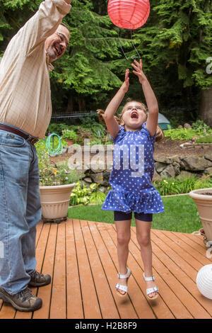 Drei Jahre altes Mädchen spielen mit einer Papierlaterne mit ihrem Großvater in Issaquah, Washington, USA - Stockfoto