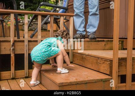 Vierzehn Monate altes Kleinkind Mädchen kämpfen, um die Holzstufen auf dem Hinterhof Zeder Deck zu klettern, als - Stockfoto
