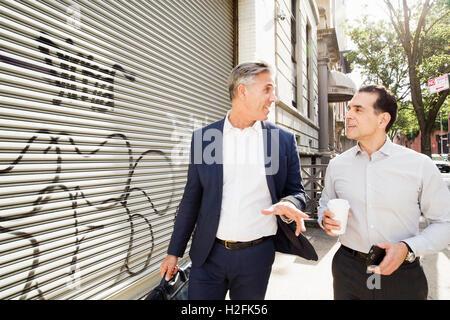 Zwei Männer zu Fuß entlang einer Straße vorbei an Stahl Verschluss an einem Gebäude mit Graffiti bemalt. - Stockfoto