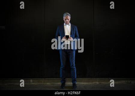 Ein Mann in einem Anzug stehen im Schatten auf einer Stadtstraße, Blick auf seinem Smartphone SMS - Stockfoto