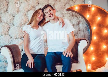 Junges Paar sitzt zu Hause umarmt - Stockfoto
