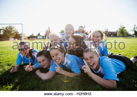 Porträt begeistert Mittelschule Mädchen Fußball Team feiert und Gestikulieren Nummer eins im Bereich - Stockfoto