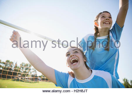 Üppige Mittelschule Mädchen Fußball Teamkollegen feiern und jubeln auf sunny Feld - Stockfoto