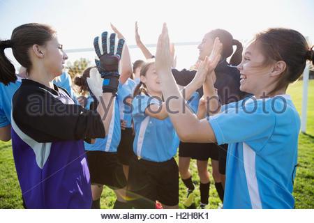 Mittelschule Mädchen Fußballmannschaft feiern hohe Fiving auf Feld - Stockfoto